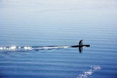 Um homem com a canoa no lago Fotografia de Stock Royalty Free