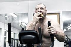 Um homem com fome gordo grande come um Hamburger com carne e queijo fotografia de stock