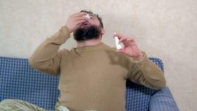 Um homem com um frio senta-se no sofá Polvilha um pulverizador nasal especial em seu nariz video estoque
