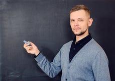 Um homem com giz perto de uma administração da escola Fotografia de Stock