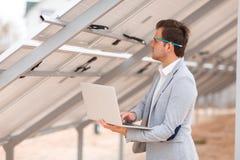Um homem com um lápis atrás de seus orelha, posses um portátil e olhares nas cablagens para os painéis solares instalou foto de stock