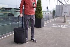 Um homem com mala de viagem e telefone celular próximo do aeroporto foto de stock royalty free