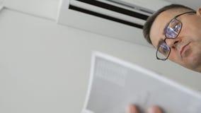 Um homem com os vidros que estão ao lado de um condicionador de ar de trabalho está estudando o manual da instrução do dispositiv video estoque