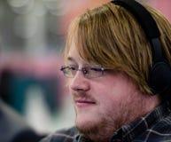 Um homem com os vidros que vestem os fones de ouvido que focalizam na frente dele foto de stock