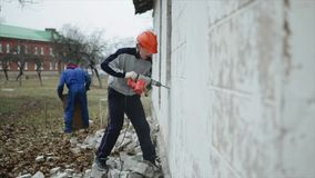 Um homem com um perfurador que quebra uma parede fora Um homem em um capacete protetor Trabalho de demolição filme
