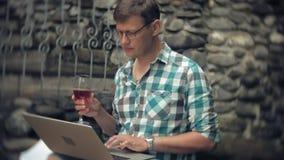 Um homem com portátil e originais no fundo de uma parede obstruir-se trabalha e bebe o vinho de um vidro vídeos de arquivo