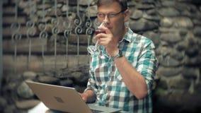 Um homem com portátil e originais no fundo de uma parede obstruir-se trabalha e bebe o vinho de um vidro filme