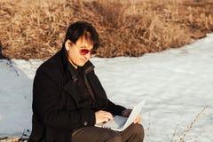 Um homem com um portátil na rua imagens de stock royalty free