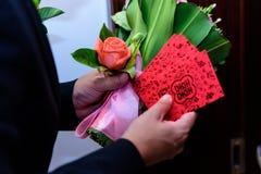 Um homem com rosas e os envelopes vermelhos Fotos de Stock