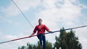 Um homem com um sexto salto fresco em uma corda esticada acima da terra Um grande feriado vídeos de arquivo