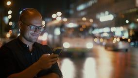 Um homem com um telefone à disposição está estando contra o fundo da condução das luzes e de carros da cidade no tráfego video estoque