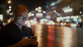 Um homem com um telefone à disposição está estando contra o fundo da condução das luzes e de carros da cidade no tráfego vídeos de arquivo