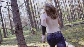 Um homem com um torso desencapado, um cabelo longo e uma faca em suas mãos que correm através das madeiras Tiro da parte traseira vídeos de arquivo