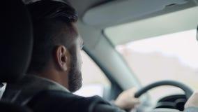 Um homem com uma barba atrás da roda de um carro Os carros baratos estão agora disponíveis a muitos video estoque