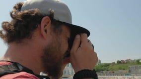 Um homem com uma barba e em uma pressão do tampão para trás faz uma foto do cais perto do mar v?deo de 4 k video estoque