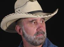 Um homem com uma barba em um chapéu de cowboy branco Imagens de Stock