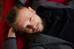 Um homem com uma barba encontra-se em um sofá vermelho que joga seu behin das mãos Imagens de Stock