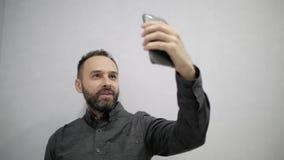 Um homem com uma barba faz um selfie no telefone video estoque