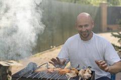 Um homem com uma barba perto do fogo e a grade fritam a carne e as salsichas Um homem novo frita um assado em uma grade em um dia Imagem de Stock