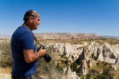Um homem com uma c?mera no fundo da paisagem da montanha de Cappadocia foto de stock