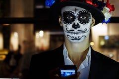 Um homem com uma cara pintada de um esqueleto, um zombi inoperante, na cidade durante o dia dia de todas as almas, dia dos mortos fotos de stock royalty free