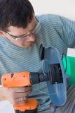 Um homem com uma chave de fenda e um ajustador para a grama foto de stock