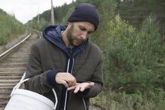 Um homem com uma cubeta dos cogumelos na floresta fotos de stock