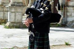 Um homem com uma gaita de fole, um kilt em uma gaiola com uma listra verde e vermelha cultura Os detalhes da saia do kilt e fotografia de stock royalty free
