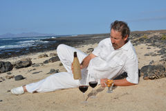 Um homem com uma garrafa do vinho e dos vidros na praia celebration Fotografia de Stock