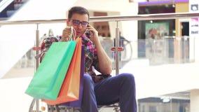 Um homem com uma inabilidade em um divertimento da cadeira de rodas que fala no telefone na alameda após a compra Fim acima video estoque