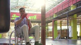 Um homem com uma inabilidade em uma fita do encaixotamento da ferida da cadeira de rodas em suas mãos no gym filme