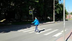 Um homem com uma inabilidade que cruza um cruzamento pedestre na cidade video estoque
