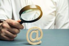 Um homem com uma lupa examina uma figura de um e-mail ou do Internet Verifique para ver se há vírus Avalie ameaças do Internet foto de stock