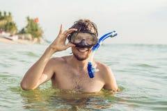 Um homem com uma máscara e um tubo de respiração está indo mergulhar no mar imagem de stock royalty free