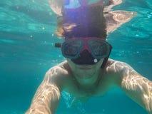 Um homem com uma máscara subaquática nada no mar Fotos de Stock Royalty Free