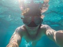 Um homem com uma máscara subaquática nada no mar imagem de stock royalty free