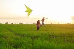 Um homem com uma menina lança um papagaio Imagem de Stock Royalty Free