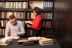 Um homem com uma mulher na biblioteca preparada para o exame leu livros Imagens de Stock