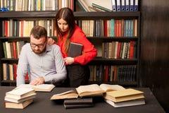 Um homem com uma mulher na biblioteca preparada para o exame leu livros Foto de Stock Royalty Free