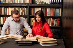 Um homem com uma mulher na biblioteca preparada para o exame leu livros Fotografia de Stock