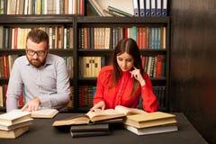 Um homem com uma mulher na biblioteca preparada para o exame leu livros Imagens de Stock Royalty Free