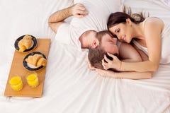 Um homem com uma mulher na manhã acordou para tomar o café da manhã na cama Imagem de Stock Royalty Free