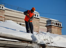 Um homem com uma pá remove a neve de um telhado Fotografia de Stock