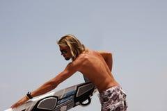 Um homem com uma placa para windsurfing. Imagem de Stock