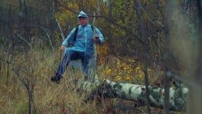 Um homem com uma trouxa em uma capa de chuva anda com as madeiras e as etapas sobre uma árvore caída filme