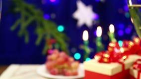 Um homem com vidros de um tim-tim da mulher com dois vidros com um champanhe no fundo de uma tabela com presentes e velas ardente filme