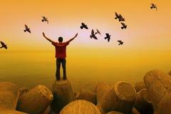 Um homem com voo dos pássaros Fotografia de Stock Royalty Free
