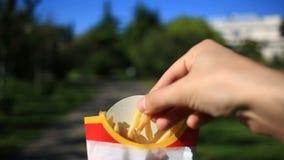 Um homem come o fast food na rua Leva batatas fritas e come-as Na perspectiva de uma cidade obscura vídeos de arquivo