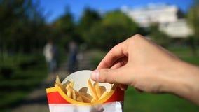 Um homem come o fast food na rua Leva batatas fritas e come-as Na perspectiva de uma cidade obscura video estoque