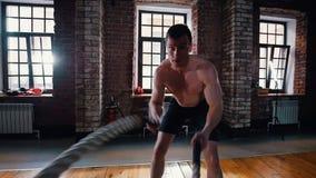 Um homem concentrado no treinamento no gym Treinando suas mãos com as cordas que batem no assoalho video estoque